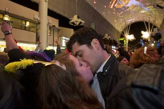 Danielle Weber and Troy Nuccio of Detroit kiss just after midnight fireworks just before midnight during the New Years Eve party at the Fremont Street Experience Tuesday, Jan.1, 2013.