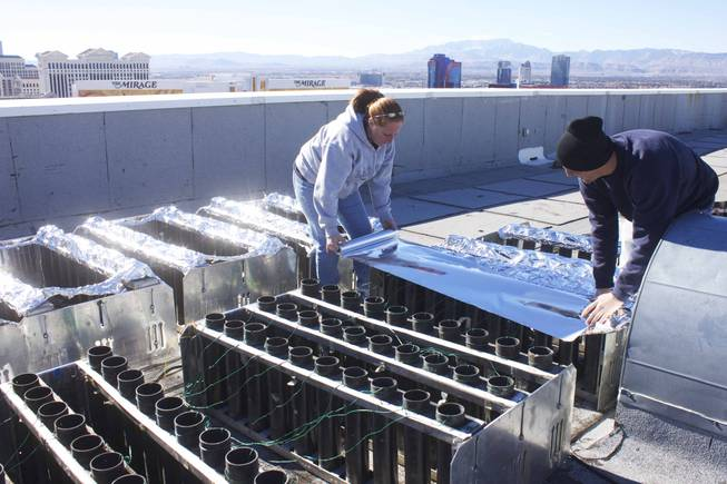 Danielle Consote-Hammond, left, and James Grucci,right, technicians for Fireworks by Grucci, cover the firework pipes with tin foil to prevent embers or any other debris from falling into them that could cause a misfire, Monday, Dec. 31, 2012.