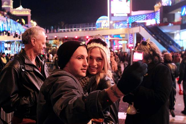 Zach Thompson and Kelli Schuh, both from Fresno, Calif., take a photo during the New Year's Eve celebration on the Strip Monday, Dec. 31, 2012.