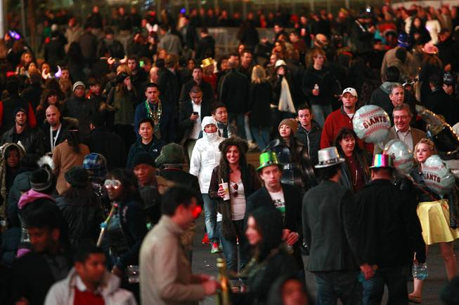 Revelers begin gathering for the New Year's Eve celebration on the Strip Monday, Dec. 31, 2012.