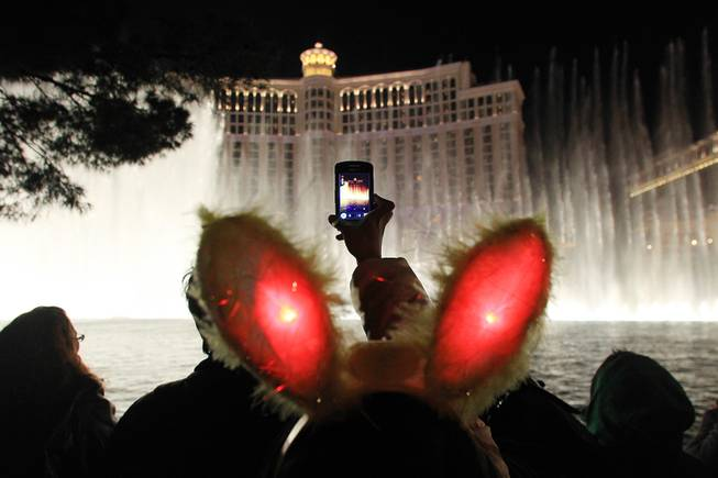 A reveler takes video of the Bellagio fountains during the New Year's Eve celebration on the Strip Monday, Dec. 31, 2012.