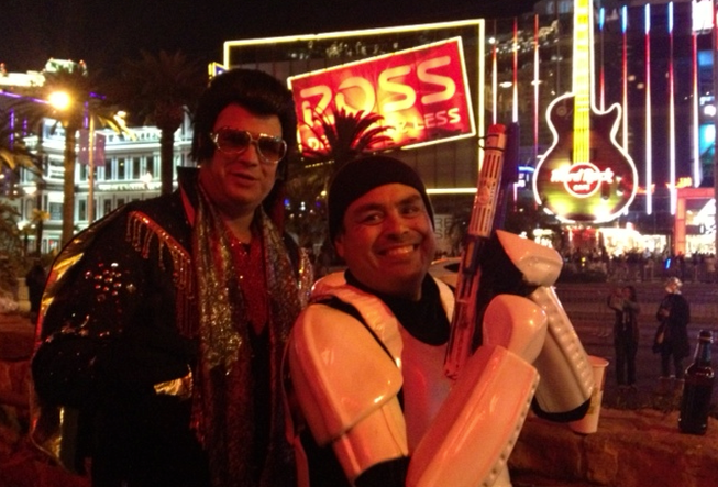 "Brett Essenmacher, as Elvis, and Ephriam Gonzalez, as a Star Wars storm trooper, stopped for a cigarette and a beer outside El Diablo bar and grill near the Monte Carlo. ""I heard you can make a lot of money out here on New Year's Eve, so I thought I'd give it a try,"" Gonzalez said."