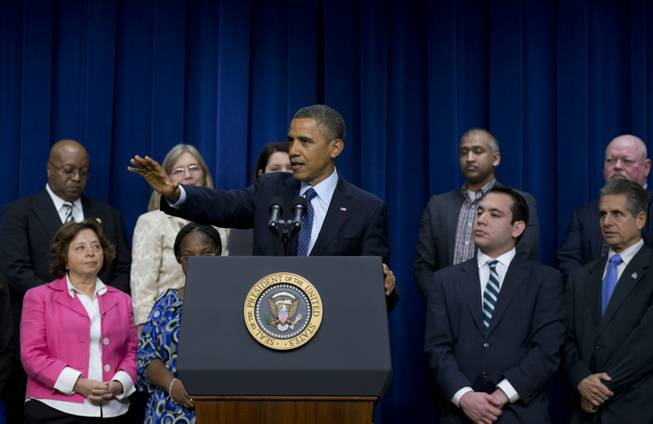 People stand behind President Barack Obama as he speaks about the fiscal cliff in the South Court Auditorium in the Eisenhower Executive Office Building of the White House complex, Monday, Dec. 31, 2012, in Washington.