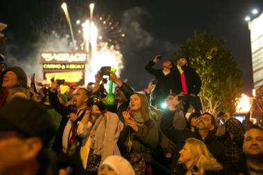 The crowd watches as fireworks fill the sky during the midnight New Year's Eve celebration on The Strip, Monday, Dec. 31, 2012.