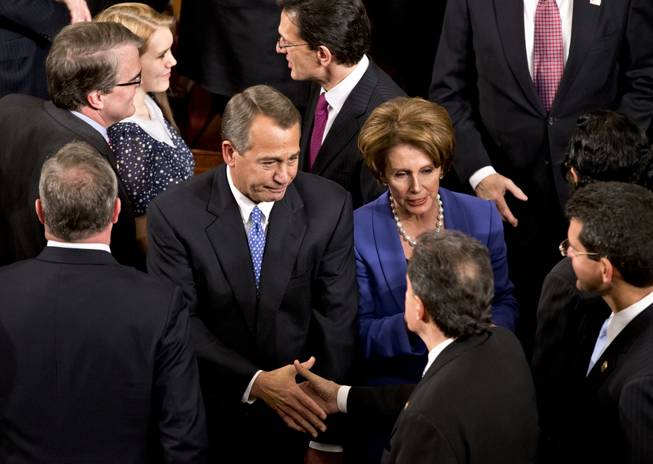 House Speaker John Boehner of Ohio enters the House of Representatives chamber on Capitol Hill in Washington, Thursday, Jan. 3, 2013, after surviving a roll call vote in the newly convened 113th Congress. He is escorted by House Majority Leader Eric Cantor of Virginia, and House Minority Leader Nancy Pelosi of California.