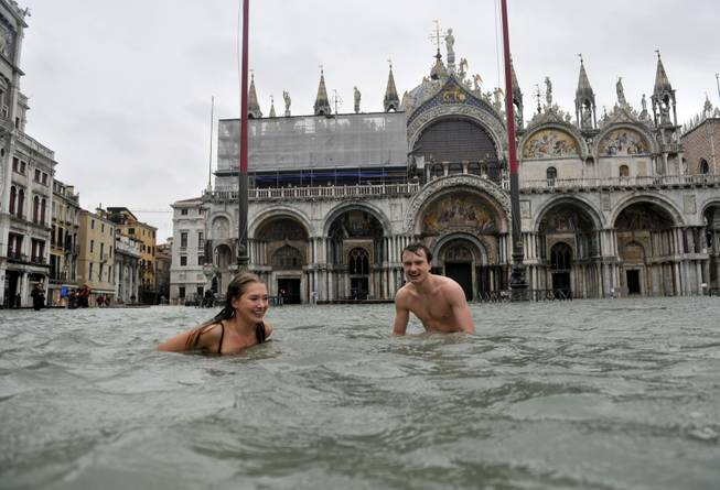 In this Nov. 11, 2012 file photo, a young man and a woman enjoy swimming in flooded St. Mark's Square in Venice, Italy. High tides flooded Venice, leading Venetians and tourists to don high boots and use wooden walkways to cross St. Mark's Square and other areas under water.