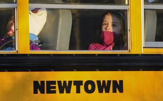 A girl sits on a Newtown bus leaving the new Sandy Hook Elementary School after the first day of classes in Monroe, Conn., Thursday, Jan. 3, 2013.  The Sandy Hook students started today in a new school, formerly called Chalk Hill School in Monroe.  It was renamed Sandy Hook Elementary and overhauled especially for the students from the Sandy Hook School shooting.