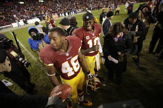 Washington Redskins quarterback Robert Griffin III,center, and teammate Alfred Morris wait to be interviewed after an NFL football game against the Dallas Cowboys on Sunday, Dec. 30, 2012, in Landover, Md. The Redskins won 28-18 to win the NFC East.
