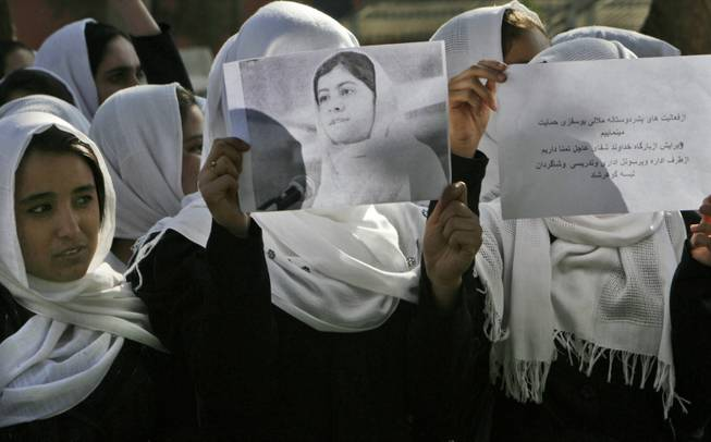 In this Saturday, Oct 13, 2012 photo, Afghan students express their support for Pakistani schoolgirl Malala Yousafzai outside their school in Herat, Afghanistan.