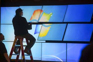 A technician works on a video wall for a Samsung booth in the Las Vegas Convention Center lobby as exhibitors prepare for the International Consumer Electronics Show in Las Vegas on Friday, Jan. 5, 2013. The show begins Jan. 8.