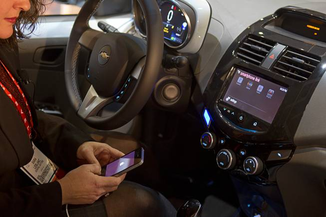 A woman links her iPhone to the MyLink system in a Chevrolet Spark at the opening press event of the 2013 International CES at the Mandalay Bay Convention Center Sunday, January 6, 2013. In addition to being able to run a variety of Apps, the system can also add incorporate Siri, which is a first for an automaker, a representative said.