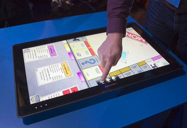 "A man tries out a Monopoly game on a Lenovo's IdeaCentre Horizon Table PC during an Intel press conference at the 2013 International CES in the Mandalay Bay Convention Center Monday, January 7, 2013. Intel announced improvements to its processors including one with ""all day"" battery life. Intel also announced the availability of live and on-demand pay TV content to Intel devices."