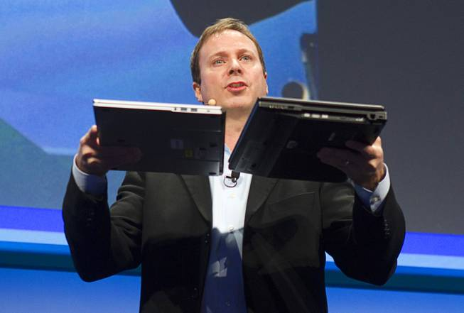 "Kirk Skaugen, Intel's vice president of PC client group, compares the thickness of a new NEC Ultrabook (12.8mm thick) and a three-year-old laptop at an Intel press conference during the 2013 International CES in the Mandalay Bay Convention Center Monday, January 7, 2013. Intel announced improvements to its processors including one with ""all day"" battery life. Intel also announced the availability of live and on-demand pay TV content to Intel devices."