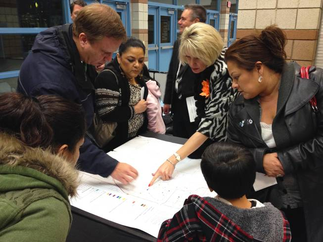 Southwest valley parents look over a school attendance zone map at Sierra Vista High School on Monday, Jan. 7, 2013. The Clark County School District held a town hall-style meeting to discuss solutions to school overcrowding, including major rezoning and reverting to an year-round schedule.
