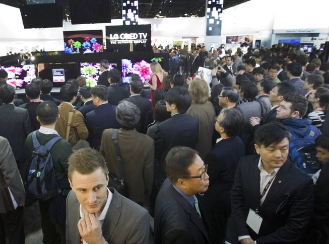 Attendees crowd displays in the LG Electronics booth during the first day of the 2013 International CES in the Las Vegas Convention Center Tuesday, Jan. 8, 2013.