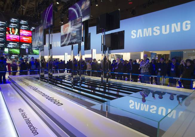 Show-goers watch a display of Samsung Smart TVs during the first day of the 2013 International CES in the Las Vegas Convention Center Tuesday, Jan. 8, 2013. The televisions have voice interaction and can make recommendations based on the consumer's viewing habits.