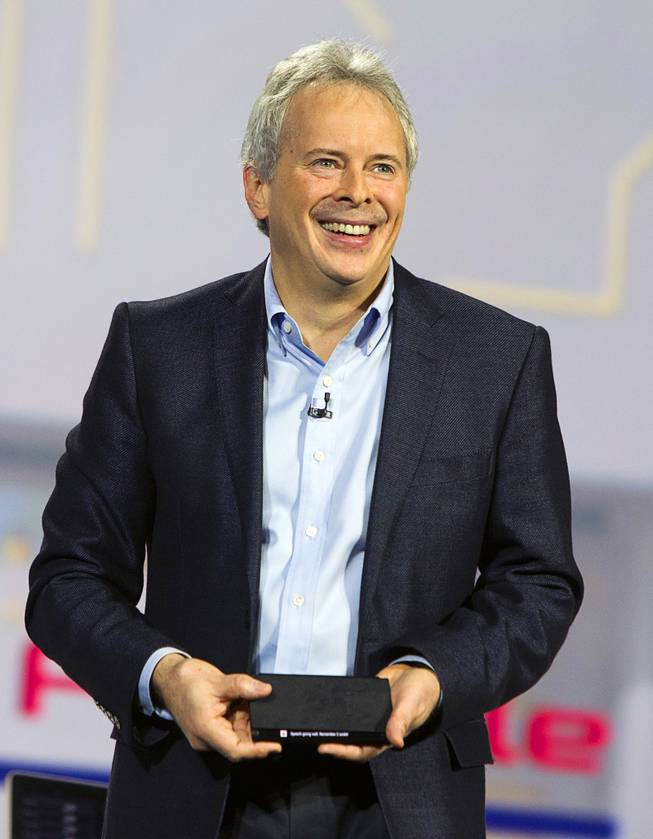 Brian Berkeley, senior vice president for Samsung's San Jose Display Lab, holds a prototype device with a wrap-around, flexible OLED screen during a keynote address at the 2013 International CES Wednesday January 9, 2013.
