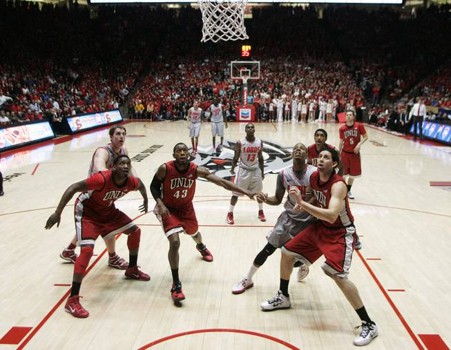 From left, UNLV forwards Quintrell Thomas, Mike Moser and Carlos Lopez-Sosa box out on New Mexico guard Jamal Fenton's free throw attempt during the second half of their game Wednesday, Jan. 9, 2013 at The Pit in Albuquerque.