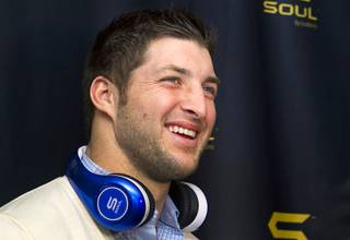 New York Jets quarterback Tim Tebow arrives at a news conference to promote Tim Tebow Signature Series headphones by Soul Electronics during the 2013 International CES on Thursday, Jan. 10, 2013.