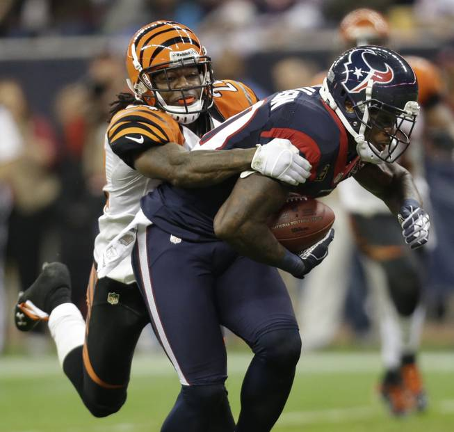 Houston Texans wide receiver Andre Johnson (80) is tackled by Cincinnati Bengals cornerback Adam Jones (24) during the third quarter of an NFL wild card playoff football game Saturday, Jan. 5, 2013, in Houston.