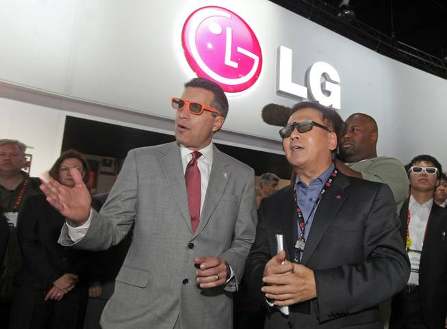 Nevada Governor Brian Sandoval, left, and Wayne Park, President and CEO LG Electronics North America, right, wear 3D glasses as they watch a demonstration of LG's revolutionary curved OLED TV shown for the first time at the 2013 International CES in Las Vegas , NV, Thursday, January 10, 2013.