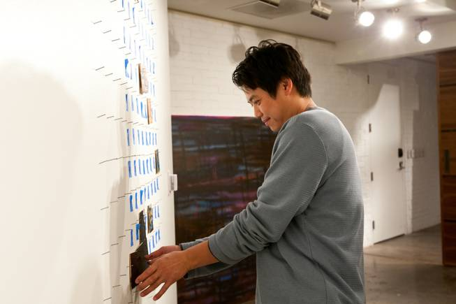 Visiting from Los Angeles, Evan Chiu, 40, hangs his painted square in its appropriate spot on pegs used to create an  iconic image of art displayed in P3Studio during James Adkins' in-house residency at The Cosmopolitan of Las Vegas Friday, January 11, 2013.