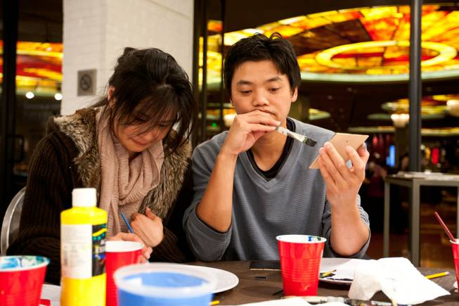 Christina Kuo, 38, and Evan Chiu, 40, of Los Angeles, concentrate while painting a square used to create an iconic image of art to be displayed in P3Studio during Artist Jason Adkins' in-house residency at The Cosmopolitan of Las Vegas Friday, January 11, 2013.