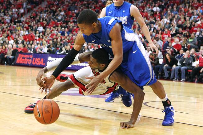 UNLV forward Mike Moser and Air Force guard Tre' Coffins hit the floor while chasing a loose ball during their game Saturday, Jan. 12, 2013 at the Thomas & Mack. UNLV won in overtime, 76-71.
