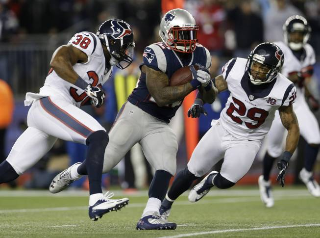 New England Patriots running back Stevan Ridley runs past Houston Texans safeties Danieal Manning (38) and Glover Quin as he scores on an eight-yard touchdown run during the second half of an AFC divisional playoff NFL football game in Foxborough, Mass., Sunday, Jan. 13, 2013.