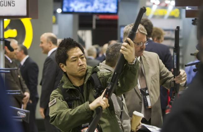 Paul Hwang of Auburn, Wash., looks over a Mossberg shotgun during the annual SHOT (Shooting, Hunting, Outdoor Trade) Show in the Sands Expo Center, Jan. 15, 2013. Gun dealers at the show are reporting booming sales resulting from worries about possible gun control legislation.