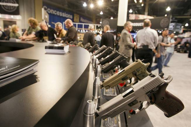 Sig Sauer handguns are displayed during the annual SHOT (Shooting, Hunting, Outdoor Trade) Show in the Sands Expo Center Tuesday, Jan. 15, 2013. Gun dealers at the show are reporting booming sales resulting from worries about possible gun control legislation. STEVE MARCUS