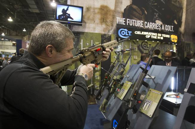 Mark Heitz, of Tactical Firearms in Kingston, N.H., looks over a civilian version of the Colt M4 carbine during the annual SHOT (Shooting, Hunting, Outdoor Trade) Show in the Sands Expo Center Tuesday, Jan. 15, 2013. Gun dealers at the show are reporting booming sales resulting from worries about possible gun control legislation. STEVE MARCUS