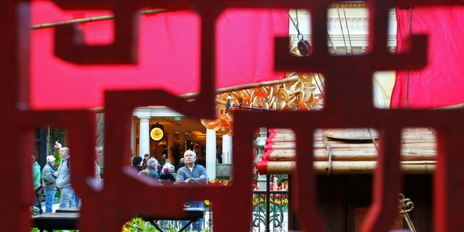 A man is seen through a Chinese wooden screen at the Bellagio Conservatory & Gardens Chinese New Year display Tuesday, Jan. 15, 2013.