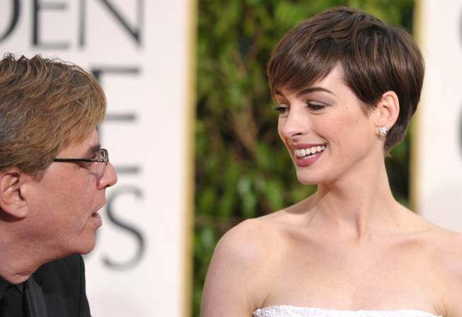Aaron Sorkin, left, and Anne Hathaway arrive at the 70th Annual Golden Globe Awards at the Beverly Hilton Hotel on Sunday Jan. 13, 2013, in Beverly Hills, Calif.