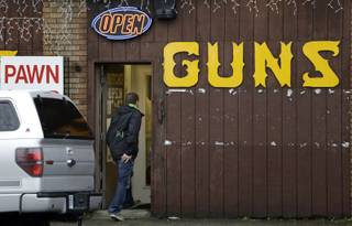 A man walks into a gun shop Wednesday, Dec. 19, 2012, in Seattle. The reaction to the Connecticut school shooting can be seen in gun stores and self-defense retailers across the nation: Anxious parents are fueling sales of armored backpacks for children while firearms enthusiasts are stocking up on assault rifles in anticipation of tighter gun control measures.