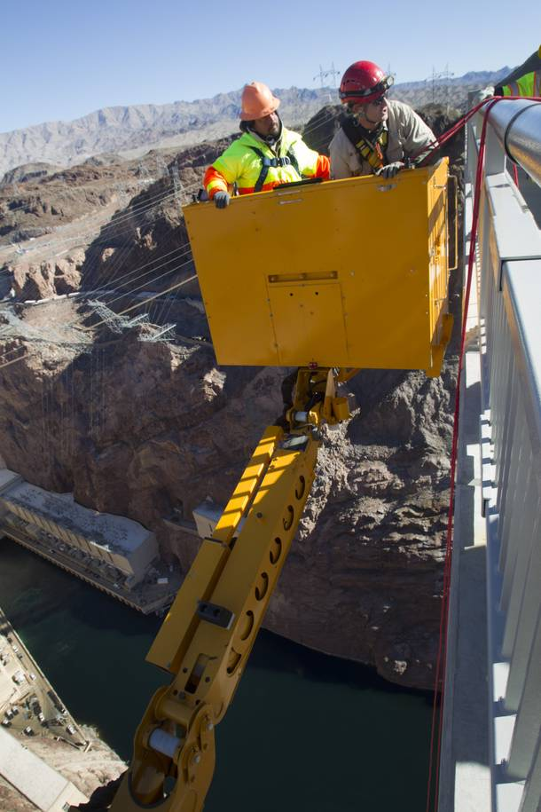 Myron Marr, a Nevada Department of Transportation bucket operator, left, and Matt Bialowas, a Stantec engineer/inspector, come up to a walkway during a safety inspection of the Mike O'Callaghan-Pat Tillman Memorial Bridge Wednesday, January 16, 2013.