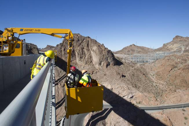 Myron Marr, a Nevada Department of Transportation bucket operator, right, and Matt Bialowas, a Stantec engineer/inspector, come up to a walkway during a safety inspection of the Mike O'Callaghan-Pat Tillman Memorial Bridge Wednesday, January 16, 2013.