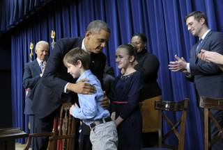 President Barack Obama, accompanied by Vice President Joe Biden, left, hugs eight-year-old letter writer Grant Fritz during a news conference on proposals to reduce gun violence, Wednesday, Jan. 16, 2013, in the South Court Auditorium at the White House in Washington. Obama and Biden were joined by law enforcement officials, lawmakers and children who wrote the president about gun violence following the shooting at an elementary school in Newtown, Conn., last month.