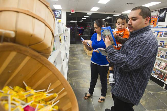 George Montes picks out movies with his son Aiden, 19-months, and his wife Rosemary at Movies & Candy, 10895 S. Eastern Ave., Thursday, January 17, 2013. Movie fan Trevor Layne opened the video shop last November when his house started overflowing with movies.