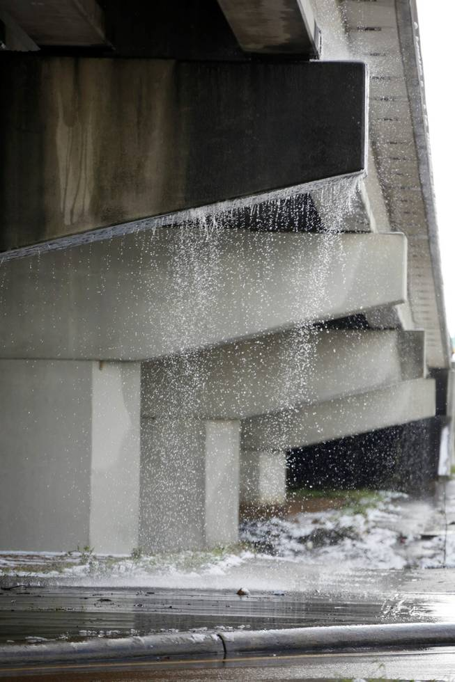 Runoff water from melting snow makes a waterfall from an overpass along I-55 in Jackson, Miss., Thursday,  Jan. 17, 2013.  A winter storm system left 2 to 4 inches of snow in parts of central Mississippi before heading east toward Alabama, the National Weather Service said.