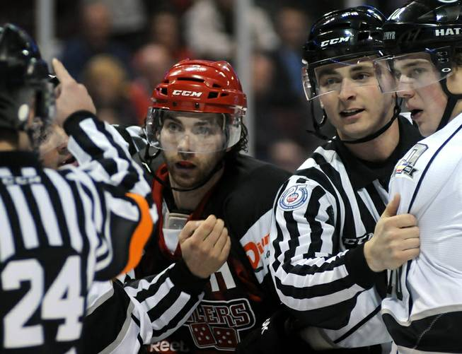 Wrangler defenseman Jamie Fritsch (center) listens as ECHL referee Andrew Wilk (left) asesses penalties to Fritsch and Colorado player Collin Bowman (right) after a small second period skirmish on Saturday night. Restraining Bowman at right is ECHL linesman Brett Martin.