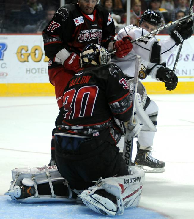Adam Huxley, left, battles for position against Norm Ezekiel as Wrangler goaltender Joe Fallon squares up to stop a Colorado shot during the second period of play at the Orleans Arena on Saturday night.