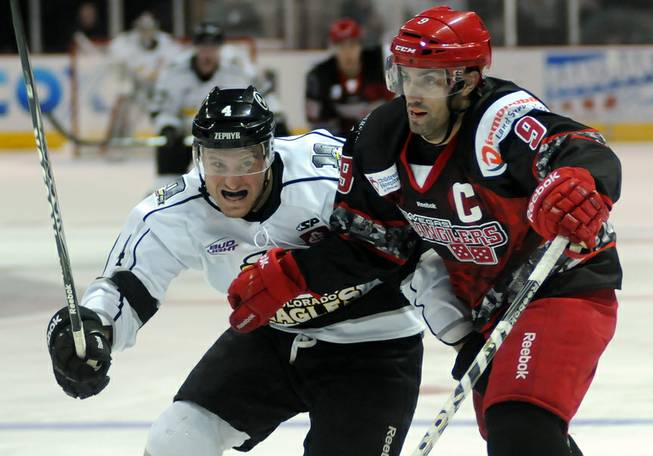 Las Vegas defenseman Mike Madill, right, slows down Isaac Smeltzer as the two enter the Wrangler defensive zone during the second period on Saturday night.
