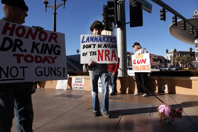 Alex Sayadi of Henderson holds up a sign during a demonstration in favor of President Obama's new gun regulations outside of the Palazzo on the Strip in Las Vegas on Saturday, January 19, 2013.