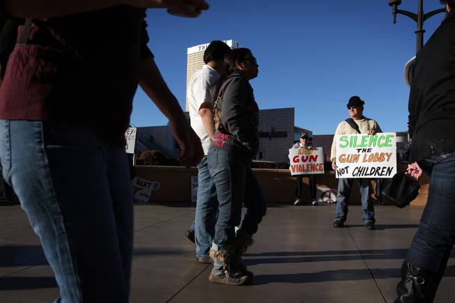 William M. Clark of Henderson holds a sign as tourists pass by during a demonstration in favor of President Obama's new gun regulations outside of the Palazzo on the Strip in Las Vegas on Saturday, January 19, 2013.