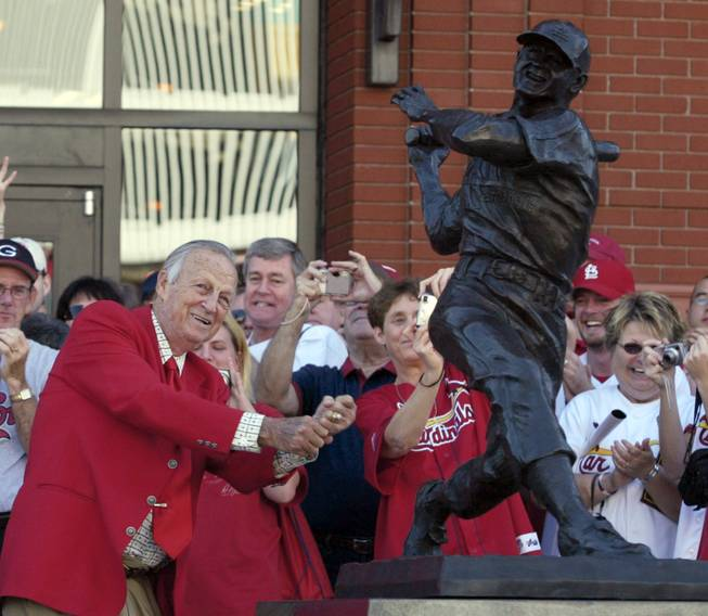 "In this Oct. 1, 2006, file photo, St. Louis Cardinals great Stan ""The Man"" Musial strikes his signature pose after unveiling his statue at the re-dedication ceremony for the statues, at the new Busch Stadium, of Cardinals Hall of Famers and notables. Musial, one of baseball's greatest hitters, died Saturday, Jan 19, 2012, the Cardinals announced. He was 92."