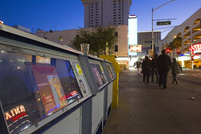 "A family passes news racks advertising adult ""entertainers"" in downtown Las Vegas, Sunday, Jan. 20, 2013."