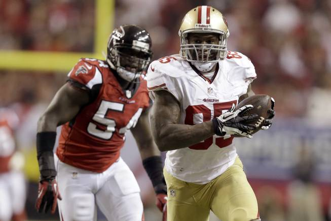 San Francisco 49ers tight end Vernon Davis carries the ball as Atlanta Falcons outside linebacker Stephen Nicholas chases him during the second half of the NFL football NFC Championship game Sunday, Jan. 20, 2013, in Atlanta.