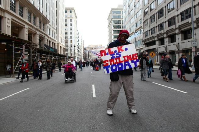 Roderick Beechum of Virgina displays a sign while walking down H Street NW in Washington, D.C., a few blocks away from the National Mall on Inauguration Day, Monday, Jan. 21, 2013.