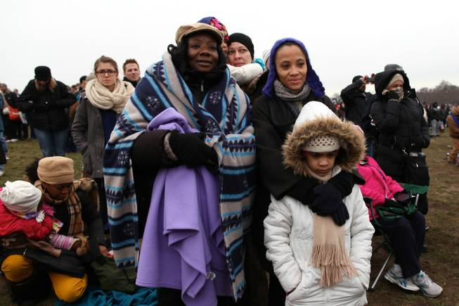 From left to right, Kimberly Graham of Jersey City, New Jersey and Natasha Bennett of New York watch the presidential inauguration ceremony on the National Mall in Washington, D.C., Monday, Jan. 2013.